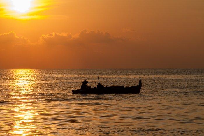 Bateau sur l'eau au coucher du soleil