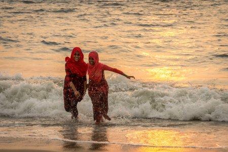 Baignade au coucher du soleil sur la plage d'Alleppey, Inde