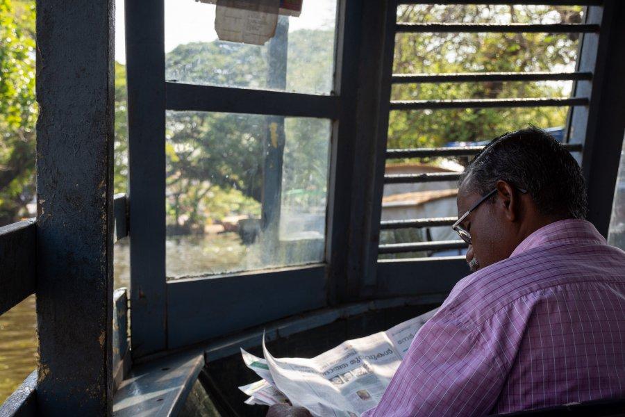 Lecture de journal sur le ferry public d'Alleppey, Kerala