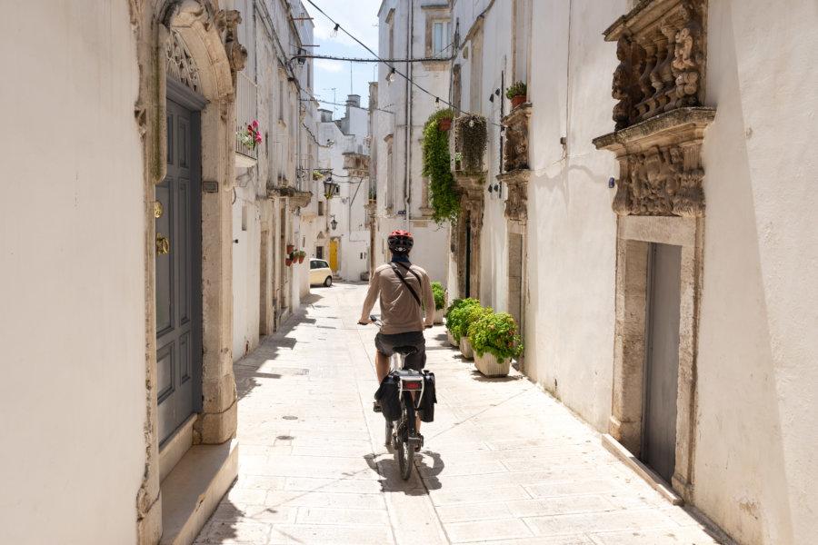 Touriste à vélo dans un village des Pouilles, Italie