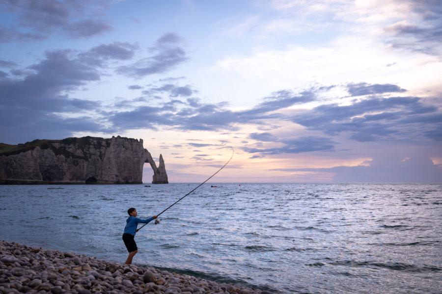 Pêcheur sur la plage d'Etretat au coucher du soleil