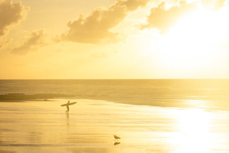 Surfeur sur la plage de Dieppe au coucher du soleil